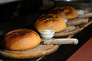 Freshly baked rolls with butter on wooden platers