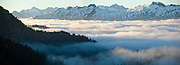 Low clouds fill the valley at sunrise at the base of Damnation Peak in North Cascades National Park, Washington. Primus Peak, Eldorado Peak, Big Devil Peak, and other mountains are visible in the distance.