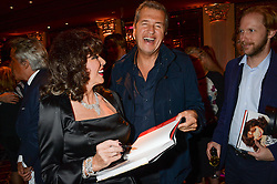 JOAN COLLINS and MARIO TESTINO at a party to celebrate the publication of 'Passion for Life' by Joan Collins held at No41 The Westbury Hotel, Mayfair, London on21st October 2013.