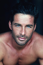 portrait of a man with stubble, blue eyes, dark hair and no shirt