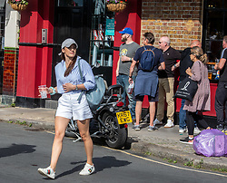 © Licensed to London News Pictures. 20/06/2020. London, UK. Crowds of pub goers gathered in Barnes in South West London as the warm weather sees members of the public go out to enjoy the sunshine and a pint or two from the Waterman's Arms in Barnes High Street where plastic containers of beer and bottles of wine are bought and then drunk outside along the banks of the River Thames. Boris Johnson is expected to give the green light for publicans to open up in the next week or two. Photo credit: Alex Lentati/LNP