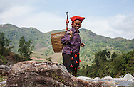 A Dao ethnic mature woman about to cross a river, smiles at the camera. Sapa, Vietnam, Southeast Asia