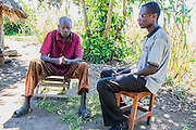 One to One Counselling.  This man lost his hands as a punishment in the war and shares his worries with one of the consellors trained by the charity. Visit to the work of Network for Africa in Patongo, Northern Uganda, November 2012.