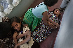 "Far right, Brianna Barthelot, 13, plays dead during a game of ""tsunami"" with friends, Batticaloa, Sri Lanka, Jan. 28, 2005. She and her sister Shrianna, 11, not pictured here, lost both parents and their older brother in the tsunami. They are now living with relatives at night and spending most of their days at the local convent where the rest of their village is staying. Residents of the small Christian village Dutch Bar spent more than six weeks in a makeshift refugee camp at the local convent recovering from the devastating tsunami that hit the eastern and southern borders of Sri Lanka. They were then moved into another temporary living camp, while awaiting the building of new homes. More than 150 members in this community of less than 1000 people died in the tragic event."