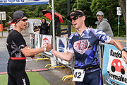 Chris Hague being congratulated by Kevin Long after he wins the male division of the 2018 Hague Endurance Festival Olympic Triathlon
