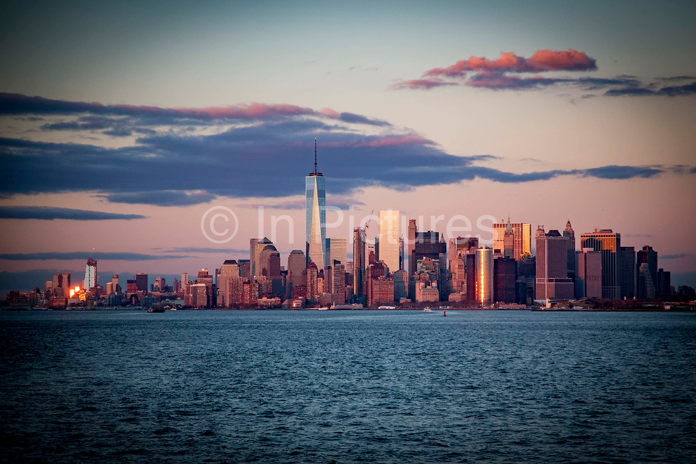 The famous skyscraper skyline of Lower Manhattan at sunset photographed from a Staten Island Ferry in Upper Bay, New York City, New York, United States of America.