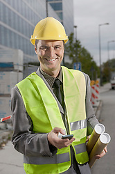 Portrait of a happy site manager holding blueprints and mobile