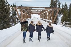Winter scene of four children walking on a snowy road towards a bridge