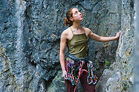 A late 20's woman looking up at a rock cliff she is about to climb.
