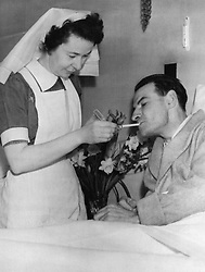 File photo dated 01/02/53 of National Health Service (NHS) nurse Nancy Lennox, lighting a cigarette for James Blair, who was rescued from the sinking of British Transport Commission's MV Princess Victoria during a storm, as he recovers in bed at Bangor Hospital, Northern Ireland.