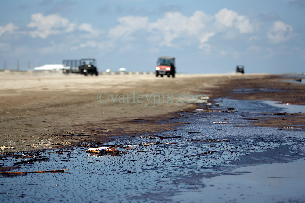 21 May 2010. Grand Isle, Lafourche Parish, Louisiana. .BP Macondo Well disaster. Oil washes ashore in greater concentrations than previously seen on the once pristine beaches of Grand Isle. The economic and environmental impact is devastating with shrimp boats tied up, vacation rentals and charter boat fishing trips cancelled as police chase tourists from the beaches just two hours drive from New Orleans..Oil from the Deepwater Horizon catastrophe is evading booms laid out to stop it thanks in part to the dispersants which means the oil travels at every depth of the Gulf and washes ashore wherever the current carries it. .Photo credit; Charlie Varley.
