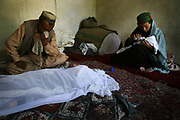 Azibullah, 30, cries next to the dead body of his wife, Qamar, center,  a 26-year-old tuberculosis patient who died of postpartum complications two weeks after the delivery, as his mother, Khalisa, at right, feeds the baby the milk in their house in the village in Shohada district in Badakshan province, Afghanistan, Monday, May 21, 2007.