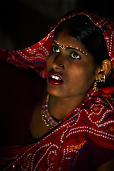 Radha, 15, waits for her groom the night of their wedding, Rajasthan, India, April 27, 2009. Three young sisters Radha, 15, Gora, 13, and Rajni, 5, were married to their young grooms Aleen, Giniaj and Kaushal, who were also siblings, on the Hindu holy day of Akshaya Tritiya, called Akha Teej in north India. The auspicious day is said to bring good luck to couples married then and is widely known in Rajasthan as the day most child marriages occur. Despite legislation forbidding child marriage in India, such as the Child Marriage Restraint Act-1929 and the much more progressive Prohibition of Child Marriage Act of 2006, marrying children off at a very tender age continues to be accepted by large sections of society.