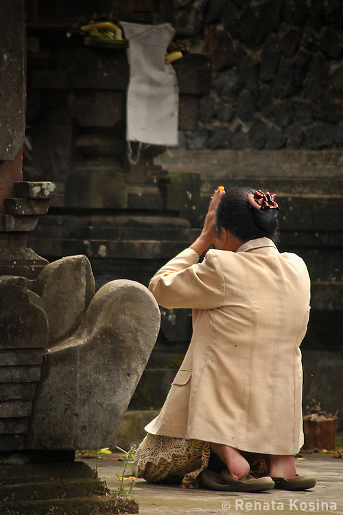 A local Balinese woman kneels down in prayer between shrines in Ulun Danu Batur temple. This pura is the second most significant in Bali and has over 100 shrines.
