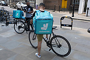 As Britain enters a period of deep recession, Deliveroo delivery couriers take a break from a busy time as the economic downturn caused by the Covid-19 pandemic cuts hard on the high street, but with some businesses doing well on 12th August 2020 in London, United Kingdom. The Office for National Statistics / ONS has announced that gross domestic product / GDP, the widest gauge of economic health, fell by 20.4% in the second quarter of the year, compared with the previous quarter. This is the biggest decline since records began. The result is that Britain has officially entered recession, as the UK economy shrank more than any other major economy during the coronavirus outbreak.