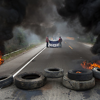 Protestors in Olancho are seen holding the Honduran flag in between plumes of black smoke rising from a burning barricade. <br /> <br /> Protests have been repressed with live fire from the armed forces and according to Human Rights group COFADEH some 40 people have been killed across the country.