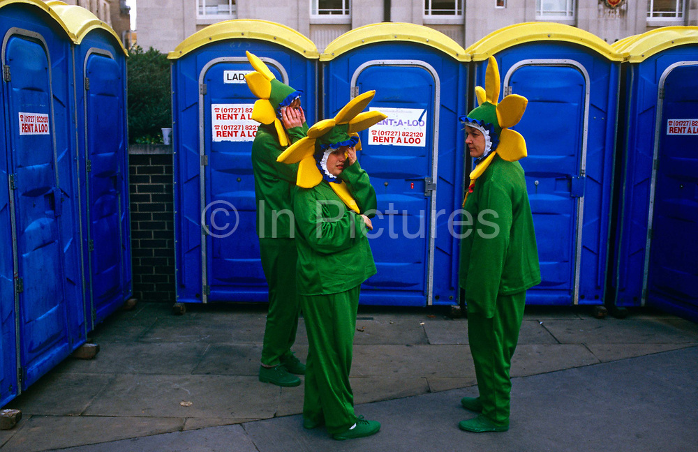 Three desperate participants of the Lord Mayor's Show in the City of London await a free portaloo cubicle. Wearing flower costumes of green with yellow-bordered headwear, the three people look fed up with waiting for a free toilet, set up during this annual event to honour the new Lord Mayor in the financial district of London.