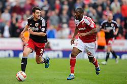 Bristol City Defender Brendan Moloney (IRL) is challenged by Swindon Midfielder Dany N'Guessan (FRA) during the first half of the match - Photo mandatory by-line: Rogan Thomson/JMP - Tel: 07966 386802 - 21/09/2013 - SPORT - FOOTBALL - County Ground, Swindon - Swindon Town v Bristol City - Sky Bet League 1.