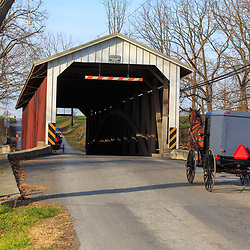Paradise, PA, USA - December 6, 2015: An Amish buggy enters the Leaman's Place Covered Bridge that spans the Pequea Creek in Lancaster County, Pennsylvania.
