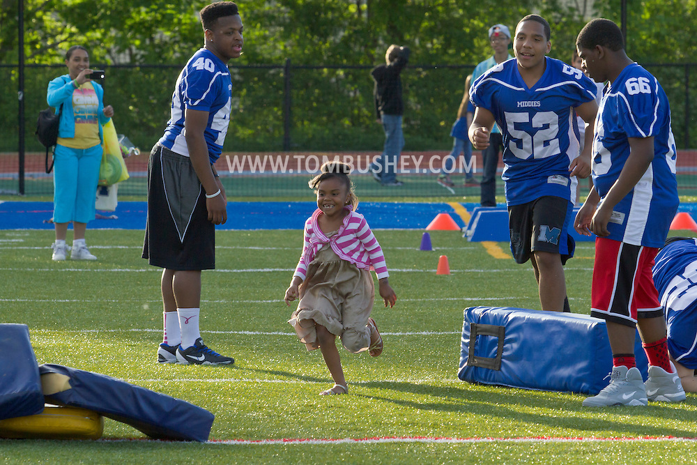 Middletown, New York - A young girl runs past Middletown High School football players at Faller Stadium during Family Fun Night on May 17, 2013.