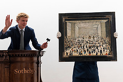 © Licensed to London News Pictures. 19/10/2021. LONDON, UK.  L.S. Lowry's 'The Auction' is presented at at Sotheby's. It is the artist's only known painting of an auction room and will make its auction debut at Sotheby's London this November with an estimate of £1.2 - 1.8 million.  Photo credit: Stephen Chung/LNP