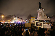 """A group of demonstrators walk with placards reading """"NOT AFRAID"""" during a massive public demonstration which took place in Place de la Republique, in central Paris, France; the evening after armed gunmen attacked the offices of Charlie Hebdo, killing twelve people, including the editor and celebrated cartoonists; four more are in critical condition. It is the dealiest terror attack in France for over fifty years. Charlie Hebdo is a satirical publication well known for its political cartoons. <br /><br />As a solidarity actions with the deaths at Charlie Hebdo many placards read """"Je suis Charlie"""" translating as """"I am Charlie (Hebdo)"""". Demonstrators held aloft pens, brushes and crayons, symbolizing the profession of journalists and cartoonists who were killed. Many pens were placed in a shrine with candles in the square"""