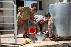© Licensed to London News Pictures. Hamdaniyah, Iraq. 26/07/2014. Christian refugee Ra'id Samir Kamal (45), formerly a driver in Mosul, waits for a bucket of water to clean his kitchen after Kurdish Zeravani soldiers distributed fresh supplies of drinking water to refugee families living in partially built houses in Hamdaniyah, Iraq. Samir left Mosul on Friday the 18th of July when Islamic State fighters issued an ultimatum to the city's Christian community. When the family left they were forced to pay a tax for their car, their son (19) was threatened at knifepoint to ensure they handed over all of their possessions including family photographs.<br /> <br /> Having taken over Mosul Iraq's second largest city in June 2014, fighter of the Islamic State (formerly known as ISIS) have systematically expelled the cities Christian population. Despite having been present in the city for more than 1600 years, Christians in the city were given just days to either convert to Islam, pay a tax for being Christian or leave; many of those that left were also robbed at gunpoint as they passed through Islamic State checkpoints.. Photo credit : Matt Cetti-Roberts/LNP