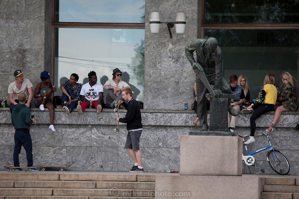 Young people skateboarding and drinking in front of the Radhus, City Hall, Oslo, Norway