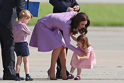 Princess Charlotte is helped up by the Duchess of Cambridge after she fell over during their visit to Airbus in Hamburg, Germany, with Prince George.