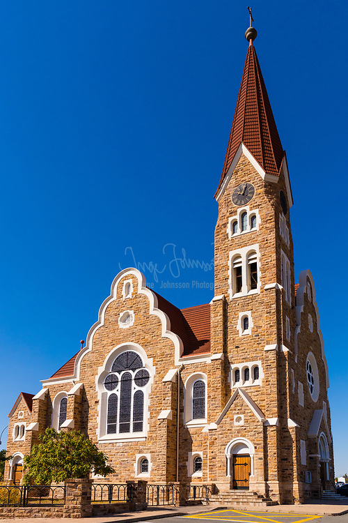 "The Christ Church (or Christuskirche) is a historic landmark and Lutheran church in Windhoek, Namibia.<br /> <br /> After the end of the wars between the Germans and the Khoikhoi, Herero, and Ovambo in 1907, the ground breaking ceremony took place and on October 16, 1910 the church was opened and dedicated as the Church of Peace. The Lutheran church, which was built in the Gothic revival style with Art Nouveau elements, stands in the historic center of Windhoek. Its 24 m high spire was made, like the rest of the church, out of quartz sandstone mined at Guche-Ganus Farm in the vicinity of present Avis Dam. The portal and the altar were made of marble from Italy. The clock and part of the roof was shipped from Germany, as were the three bronze bells cast by Franz Schilling. They bear the inscriptions ""Ehre sei Gott in der Höhe"" (Glory to God in the highest), ""Friede auf Erden"" (Peace on earth), and ""Den Menschen ein Wohlgefallen"" (Goodwill towards men). During a confirmation service in the 1960 the clapper of the main bell came loose, smashed through the window and fell on the street. Window bars were installed in reaction to this.<br /> <br /> The colorful stained lead glass windows in the sanctuary were a gift from Emperor Wilhelm II. In the late 1990s a tourist noticed that all of them were installed with the sun protection on the inside. In the two years following this discovery, all window elements were restored and turned around.<br /> <br /> The Church is located on Fidel Castro Street near the Parliament Gardens and Tintenpalast."