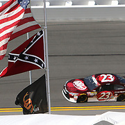 Sprint Cup Series driver J.J. Yeley (23) speeds through turn 4 where a confederate flag is posted during the 57th Annual NASCAR Coke Zero 400 practice session at Daytona International Speedway on Friday, July 3, 2015 in Daytona Beach, Florida.  (AP Photo/Alex Menendez)