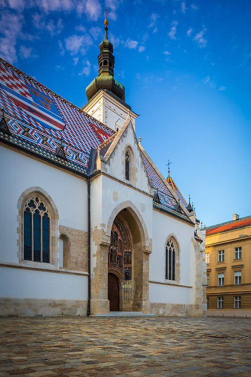 The colourful Church of St. Mark is one of the oldest buildings in Zagreb and of its symbols. It is first mentioned in the list of parish churches in the Kaptol Statute of 1334.<br /> <br /> It was built in the 13th century; from that first, Romanesque period, only a window in the south wall and the bell-tower foundation are preserved. Gothic arches and the shrine were built in the second half of the 14th century, when the church got its most valuable part - luxurious Gorhic south portal. In terms of figures it contains, that Gothic portal is one of the most beautiful one in Croatia. It was made in the Parler workshop, one of the most famous medieval sculpting workshops. The north - western wall contains the oldest known coat - of - arms of Zagreb from 1499.<br /> <br /> The church was thoroughly reconstructed in the second half of the 19th century, based on the designs of Viennese architects Friedrich Schmidt and Hermann Bolle. It underwent another reconstruction in the first half of the 20th century. At that time, renowned painter Jozo Kljakovic (1888 - 1969) painted its walls, while the altar was decorated with works of famous sculptor Ivan Mestrovic.