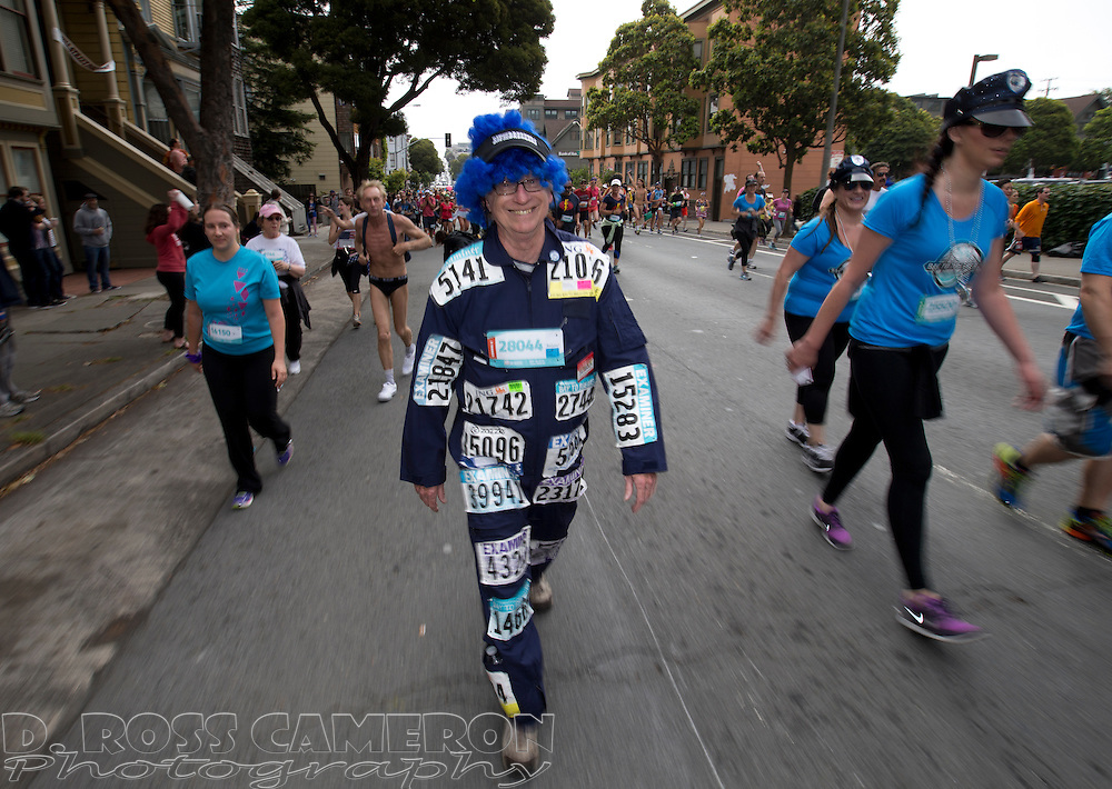 Bradford Lee of Concord, Calif., center, who said that he's been participating in the Bay to Breakers since 1993, wears all of his bibs from over the years as he makes his way up Fell Street during the 103rd iteration of the iconic 12K race, Sunday, May 18, 2014 in San Francisco. (Photo by D. Ross Cameron)