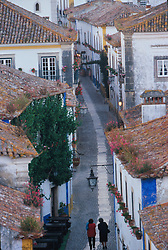 Europe, Portugal, Obidos, women walking in cobblestone alley, viewed from above