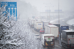 © Licensed to London News Pictures. 27/02/2018. Maidstone, UK.  Lorries queue up coast bound on the M20 north of Maidstone as snow continues to fall. Freezing temperatures and heavy snow are affecting large parts of Kent.  Photo credit: Peter Macdiarmid/LNP