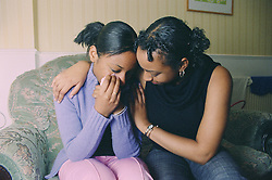 Teenage girl sitting on sofa crying; being comforted by older sister,