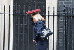 London, June 27th 2017. Education Secretary Justine Greening, protecting her head from a sudden downpour, leaves the weekly UK cabinet meeting at 10 Downing Street in London.