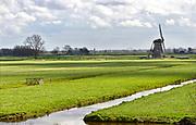 Nederland, Kinderdijk, 30-3-2018 Typisch nederlands, hollands, landschap met groene weilanden in polders, water in sloten en een klassieke molen, windmolen . . Foto: Flip Franssen