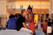 Young couples at sunset on the sea wall bordering the port (Malecón) in old Havana, Cuba.