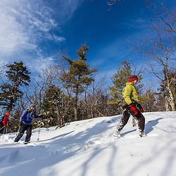 Hikers on the Hanson Trail in winter. Hanson Top on Green Mountain. Effingham, New Hampshire.