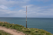 View out to sea past a metal cross from the coastal path on 17th August 2021 in Newport, Pembrokeshire, Wales, United Kingdom. Newport is a town, parish, community, electoral ward and ancient port of Parrog, on the Pembrokeshire coast in West Wales at the mouth of the River Nevern in the Pembrokeshire Coast National Park.