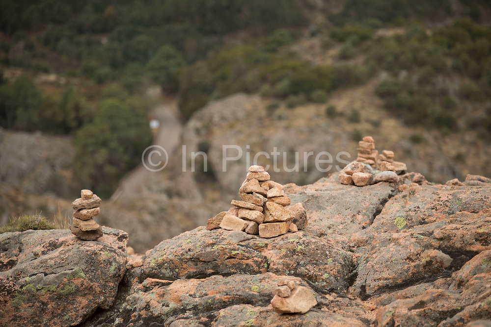 Pile of rocks in a mountain landscape of the Calanques de Piana, gold and pink coloured granite rock formations formed by wind and rain erosion creating dramatic cavities as they descend into the sea at the gulf of Porto on 11th September 2017 in Piana, Corsica, France. Corsica is an island in the Mediterranean and one of the 18 regions of France. It is located southeast of the French mainland and west of the Italian Peninsula.