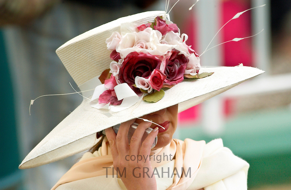 Race-goer wearing a cream hat trimmed with flowers at Royal Ascot Races while chatting on her mobile cell phone.
