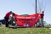 Jim Frazier and Pete Sanders of CWA Local 13000 put up a banner while picketing outside a Verizon Wireless store near Bloomsburg, Pennsylvania.
