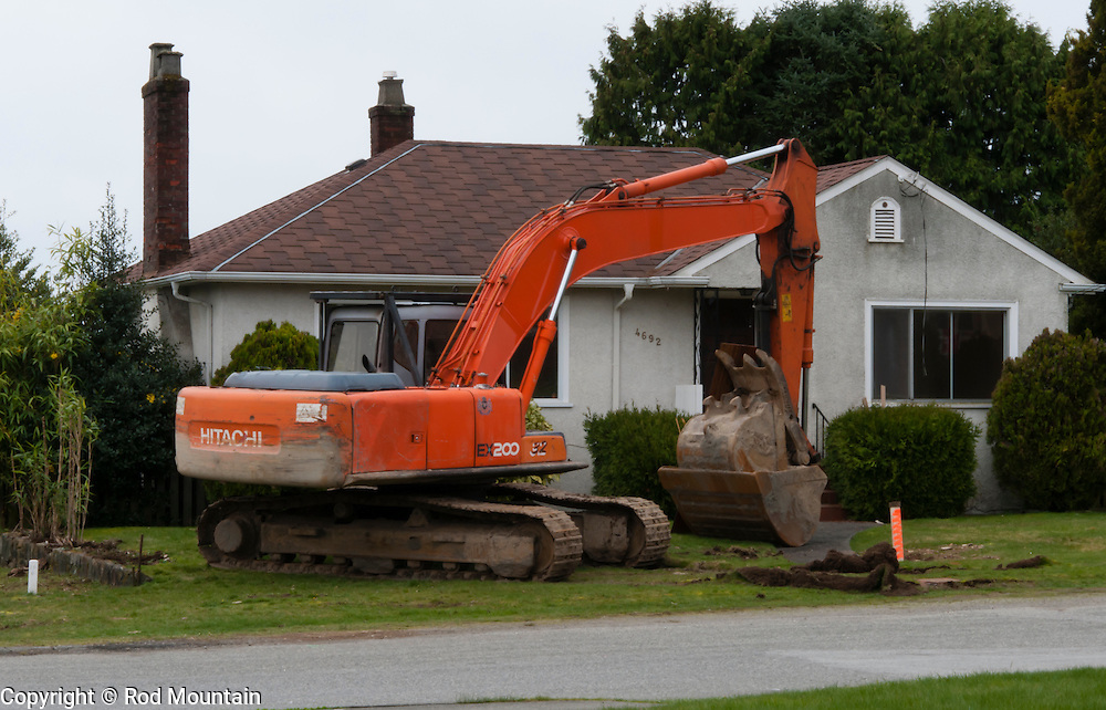 A backhoe sits on the front lawn of a residence in Burnaby, British Columbia