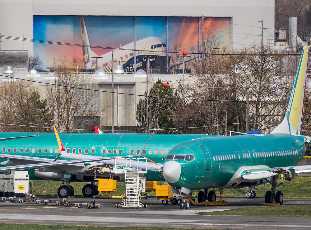 Unfinished Boeing 737 Max jets outside the Boeing Renton Assembly plant, Renton, WA, US, on 3/22/2019.  Large mural on factory door, above, portrays a 737 MAX.