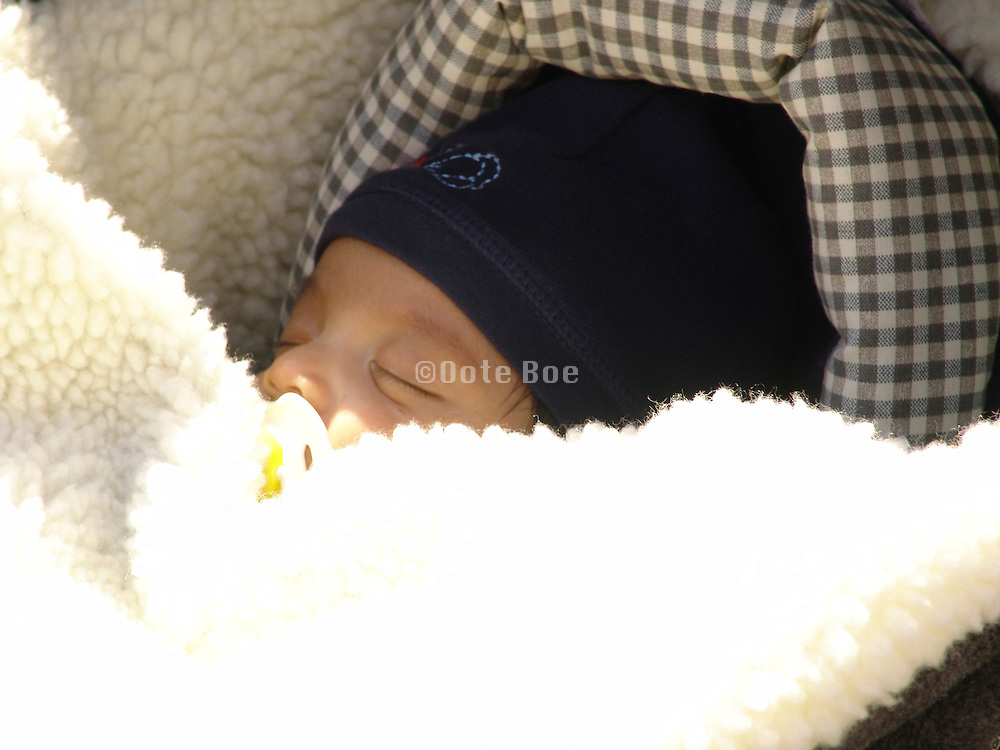 Close up of a toddler asleep in his stroller