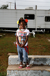 29 August 2007. Lower 9th Ward, New Orleans, Louisiana. <br /> Second anniversary of Hurricane Katrina. Robert Lynn Green Sr's  grand daughter Chayana Hurst (4 yrs) on the steps of 1826 Tennessee Street in front of her grandfather's trailer in the Lower 9th Ward. The steps are all that remain of his house after it was deluged by the levee breach just blocks from the steps. Robert lost his mother and another grand daughter at the house when they perished in the terrible flooding. He lost hold of his grand daughter in the swirling floods. She was drowned. His mother was not found for 4 months when her skeleton was discovered in what remained of his washed away house. Jason hopes to rebuild. Many residents are struggling to return to the still derelict and decimated Lower 9th Ward.<br /> Photo credit©; Charlie Varley/varleypix.com