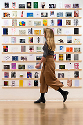 © Licensed to London News Pictures. 08/04/2016. A member of staff views The Royal College of Arts(RCA) 22nd annual Stewarts Law RCA Secret exhibition of postcards designed by well-known artists and designers. London, UK. Photo credit: Ray Tang/LNP