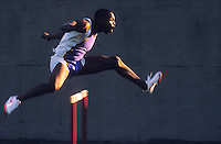 African American man on track running over a hurdle.<br />
